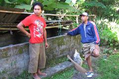 Gedeh Wangah en zijn broer Made voor de varkenshokken