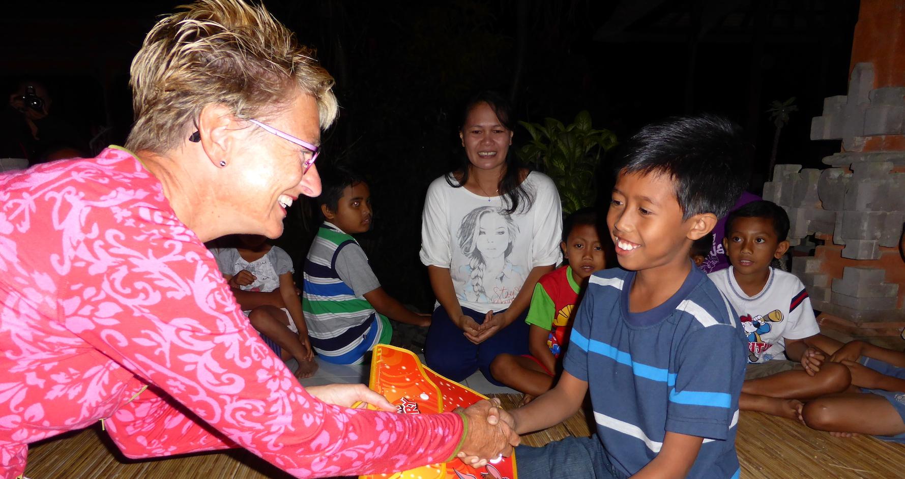 Budakeling Kinderen naar school 6 Caroline deelt schoolpakketten uit